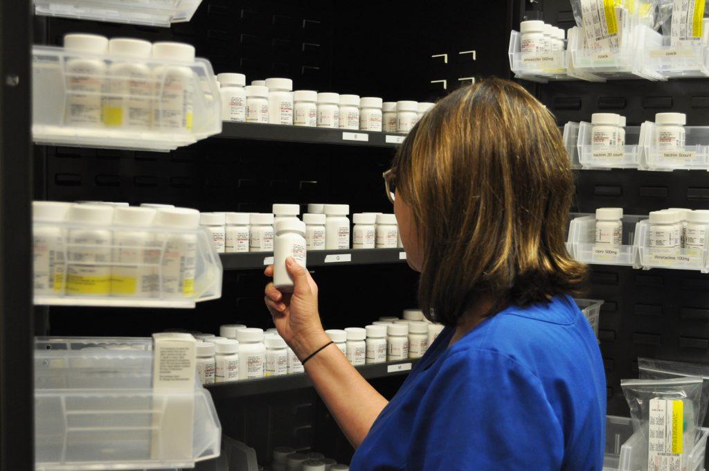 Medical assistant inspects prescription medicines in clinic medicine closet