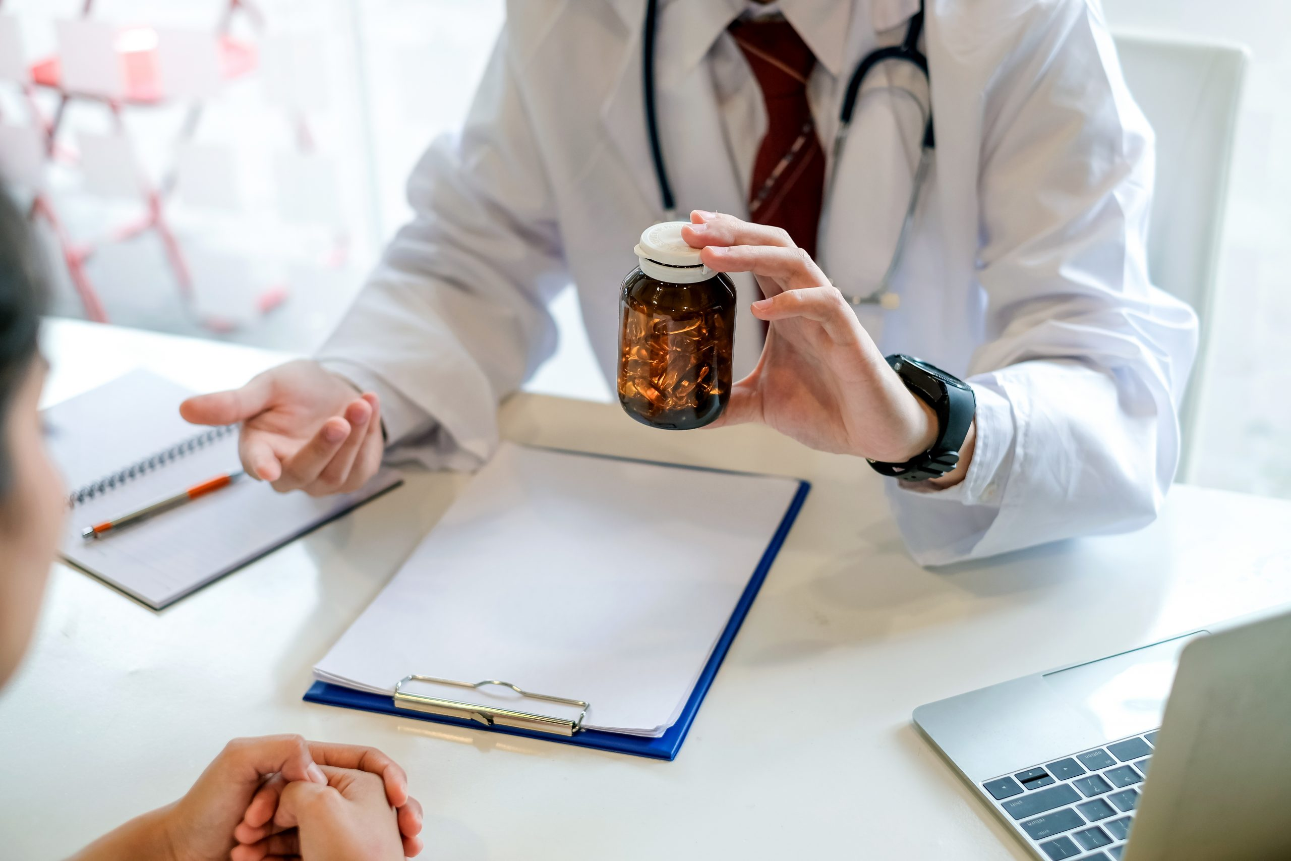 Onsite Medication Dispensing: Medical provider at desk shows pill bottle to patient