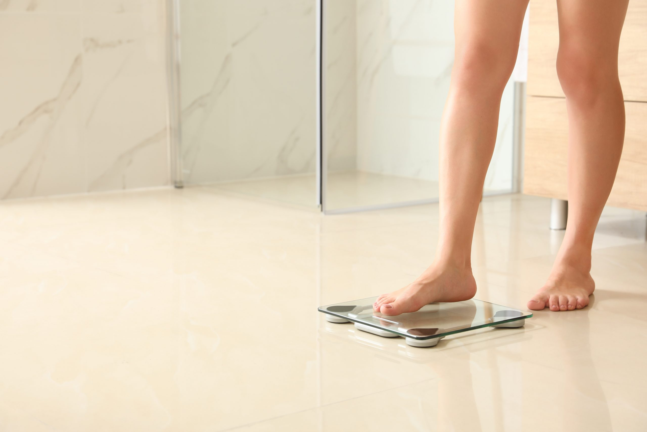 Symbol Weight Management Programming: Woman steps on scale at home